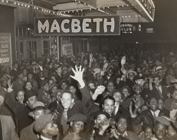 An eager audience before a theatre showing Macbeth